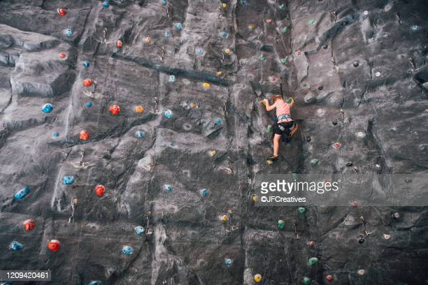low angle view of young boy ascending rock climbing wall in bolzano, lombardy, italy. - クライミングウォール ストックフォトと画像
