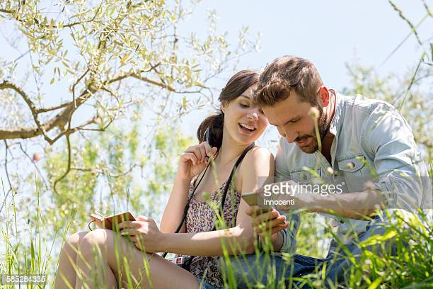 Low angle view of young couple sitting looking down at smartphone smiling