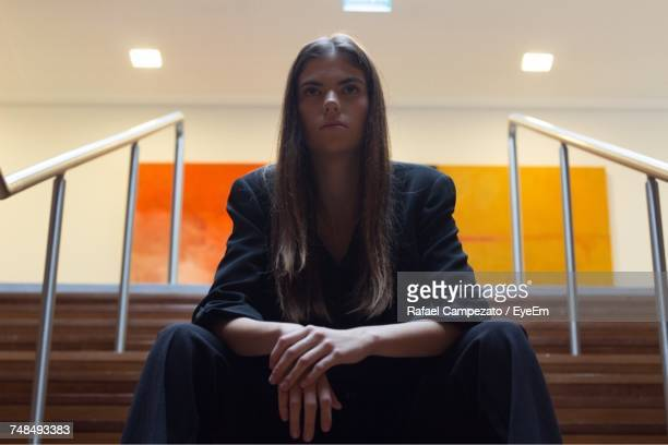 Low Angle View Of Young Fashion Model Sitting On Steps Against Illuminated Building