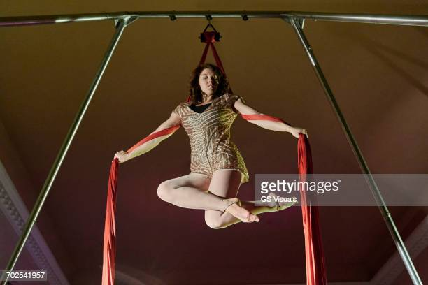Low angle view of young female aerial acrobat poised with silk rope