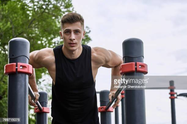 Low angle view of young male athlete exercising on parallel bars against sky