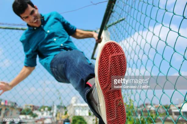 Low Angle View Of Young Man Climbing Chainlink Fence