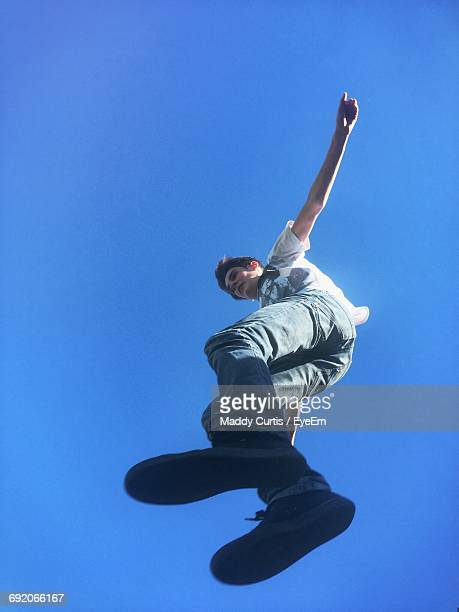 low angle view of young man jumping against clear blue sky - vista de ángulo bajo fotografías e imágenes de stock