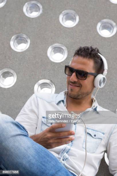 Low Angle View Of Young Man Listening Music Through Headphones While Sitting Outdoors