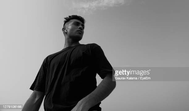low angle view of young man looking away against sky - eyeem collection stock pictures, royalty-free photos & images