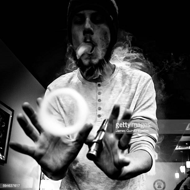 Low Angle View Of Young Man Making Smoke Ring Using Electronic Cigarette In Restaurant