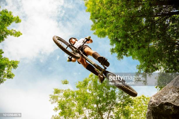 Low Angle View Of Young Man Performing Stunt With Bicycle Against Sky At Park