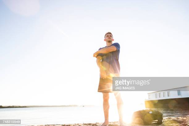Low angle view of young man preparing for training on sunlit beach