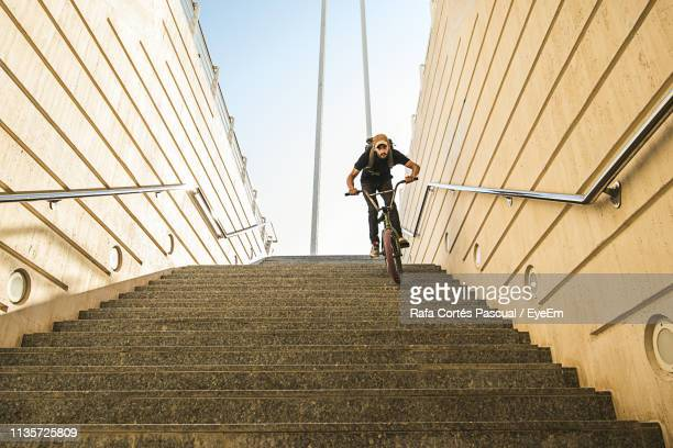 low angle view of young man riding bicycle on steps - danger stock photos and pictures