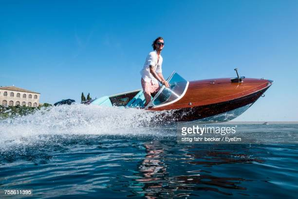 low angle view of young man riding speedboat on sea against clear blue sky - nautical vessel stock pictures, royalty-free photos & images