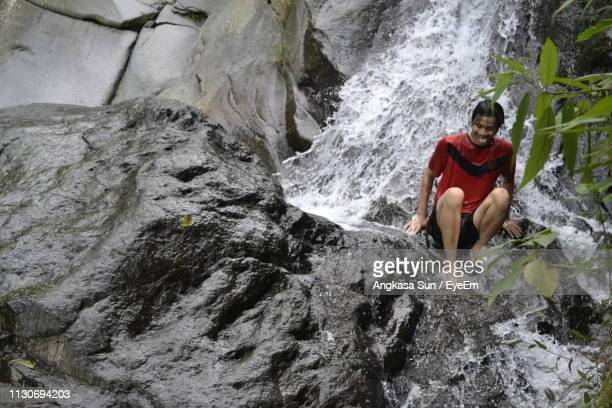 Low Angle View Of Young Man Sitting On Rock In Waterfall
