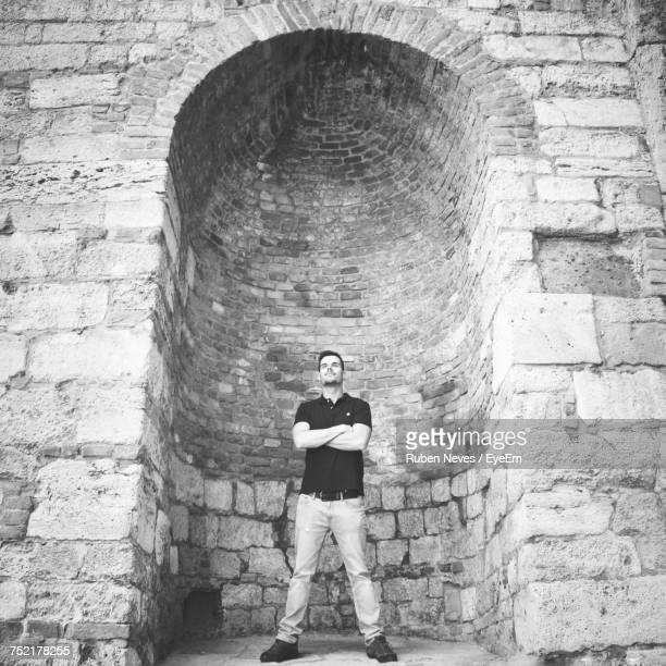 Low Angle View Of Young Man Standing Against Arch At Historic Building
