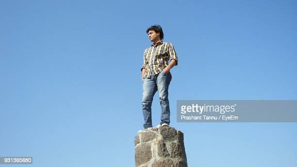 Low Angle View Of Young Man Standing Against Clear Blue Sky