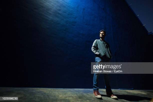 low angle view of young man standing against wall at night - low angle view stock pictures, royalty-free photos & images