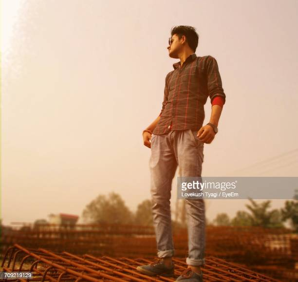 Low Angle View Of Young Man Standing On Metallic Rods At Construction Site