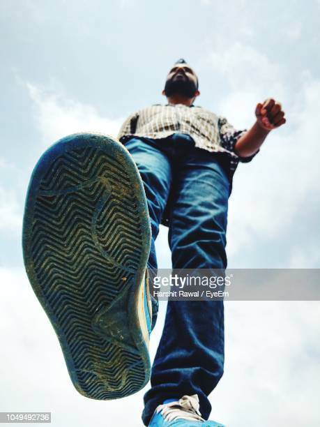 low angle view of young man walking against sky during sunny day - vista de ângulo baixo - fotografias e filmes do acervo