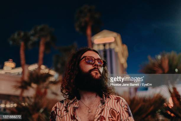 low angle view of young man wearing sunglasses against sky at night - las vegas stock-fotos und bilder