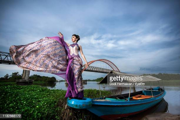 low angle view of young model wearing dress while standing on boat in river against cloudy sky - central kalimantan stock pictures, royalty-free photos & images