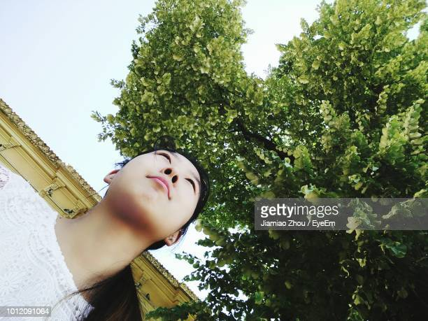 Low Angle View Of Young Woman Against Trees