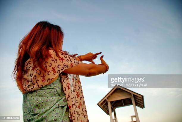 Low Angle View Of Young Woman Gesturing While Standing Against Sky