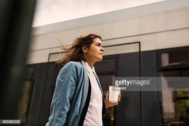 Low angle view of young woman holding disposable cup while walking by tram