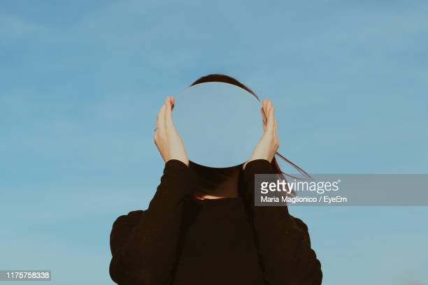 low angle view of young woman holding mirror against blue sky - 鏡 ストックフォトと画像