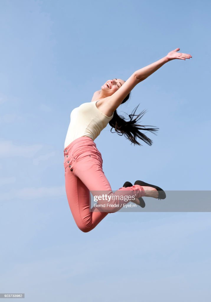 Low Angle View Of Young Woman Jumping Against Sky : Stock-Foto