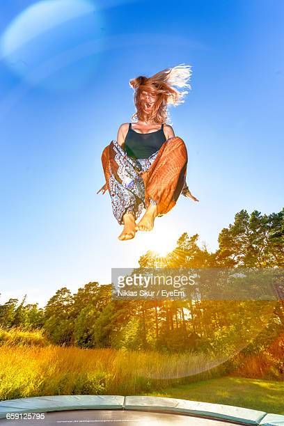Low Angle View Of Young Woman Jumping On Trampoline
