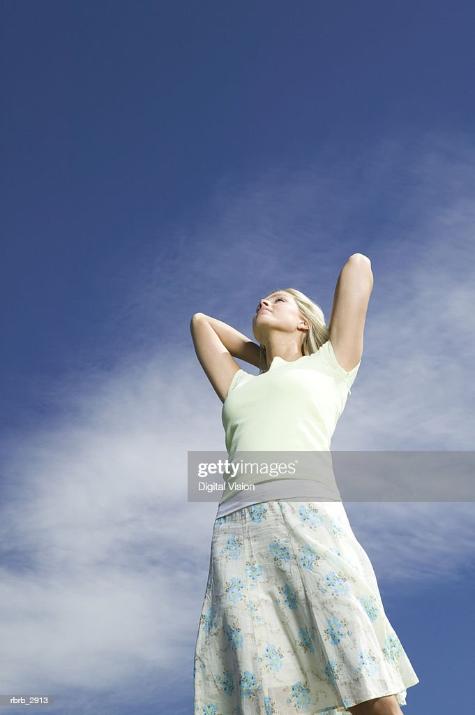 Low angle view of young woman looking up with hands behind her head : Foto de stock