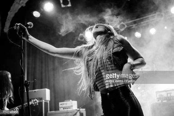 low angle view of young woman on stage - singer stock pictures, royalty-free photos & images