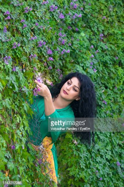 low angle view of young woman plucking flower from plants - black hair stock pictures, royalty-free photos & images