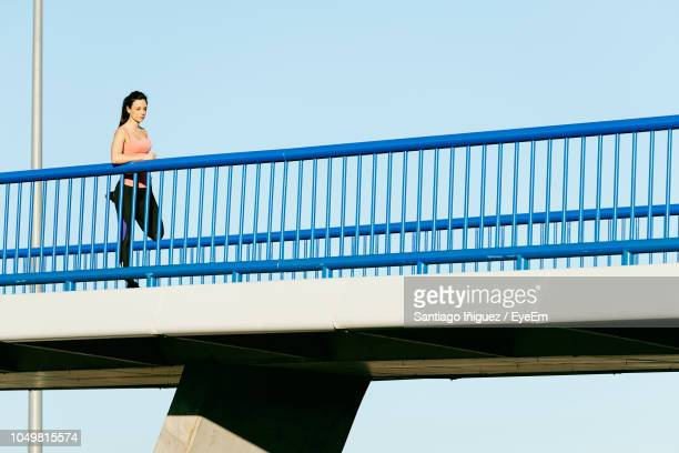 low angle view of young woman running on footbridge against clear sky - 歩道橋 ストックフォトと画像