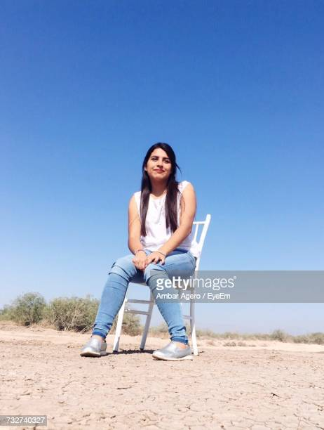 Low Angle View Of Young Woman Sitting On Chair Against Clear Blue Sky During Sunny Day