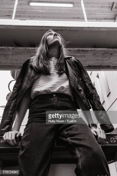Low Angle View Of Young Woman Sitting On Railing