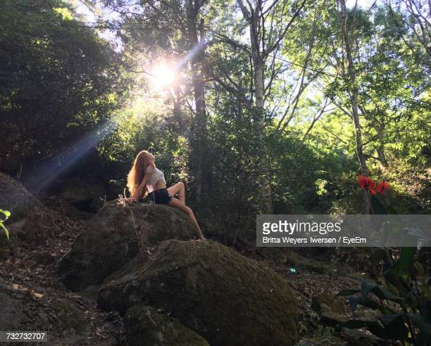 low angle view of young woman sitting on rock at forest - monchique stock pictures, royalty-free photos & images