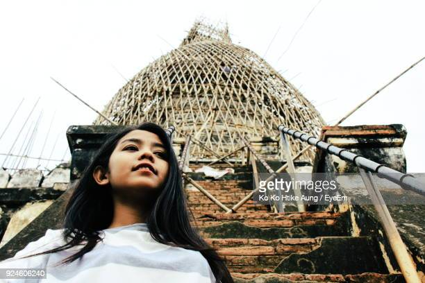 low angle view of young woman standing against built structure - ko ko htike aung stock pictures, royalty-free photos & images