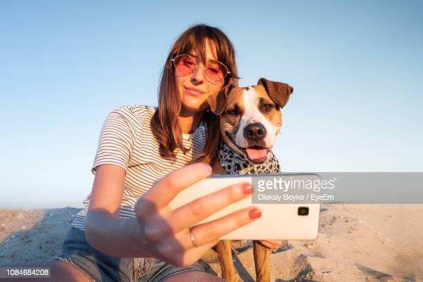 low angle view of young woman taking selfie with dog through smart phone at beach against clear sky - um animal - fotografias e filmes do acervo