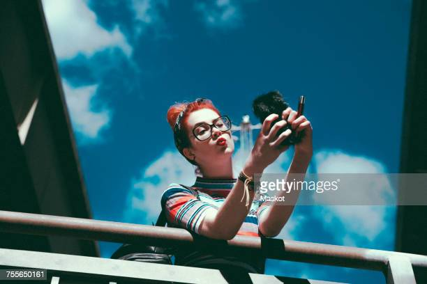 Low angle view of young woman taking selfie with mobile phone while leaning on railing against sky