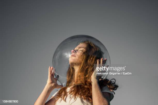 low angle view of young woman wearing glass helmet in head against gray background - ver através - fotografias e filmes do acervo