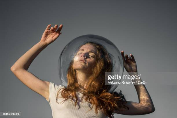 low angle view of young woman wearing glass helmet in head against gray background - personas cabeza grande fotografías e imágenes de stock