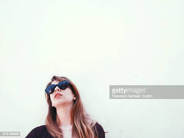 Low Angle View Of Young Woman Wearing Heart Shape Sunglasses Against White Background