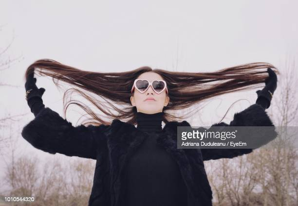 Low Angle View Of Young Woman Wearing Heart Shape Sunglasses While Standing Against Clear Sky During Winter