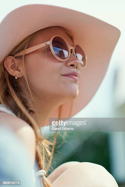Low angle view of young woman wearing sunglasses and hat