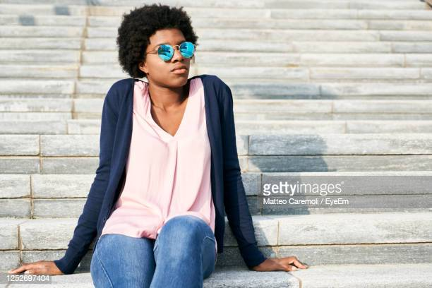 low angle view of young woman wearing sunglasses sitting on staircase - black jeans foto e immagini stock
