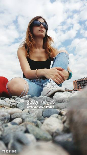Low Angle View Of Young Woman Wearing Sunglasses While Sitting Against Sky