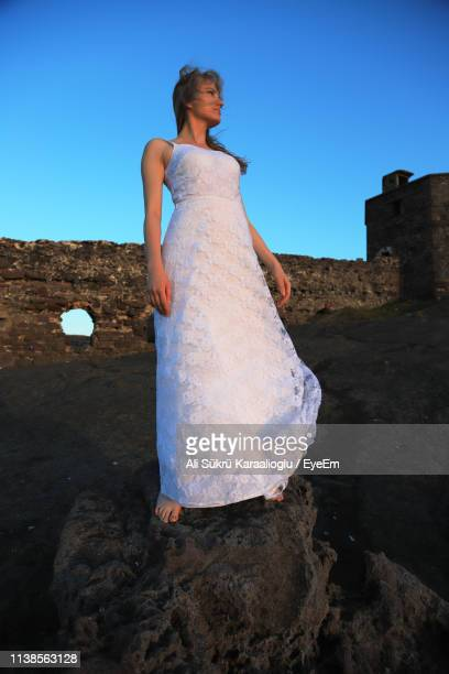 low angle view of young woman wearing white dress standing on rock against sky - 白のドレス ストックフォトと画像