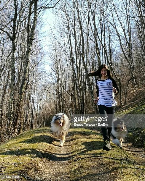 Low Angle View Of Young Woman With Dogs Running Down On Hill