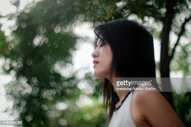 low angle view of young woman with eyes closed standing in park - ミディアムヘア ストックフォトと画像