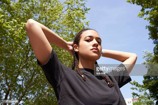 low angle view of young woman with hands behind head - attitude stock pictures, royalty-free photos & images