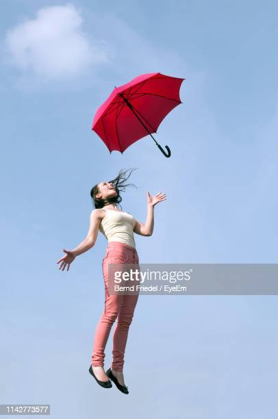 low angle view of young woman with red umbrella levitating against sky - 空中 ストックフォトと画像